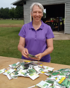 More paperwork...Susan choosing from the free seeds that are in the community garden shed. Please help yourselves. These seeds were donated by Sue Johnson from Seeds for Peace. Thank you.